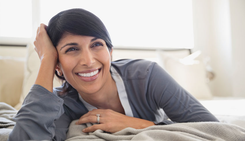 Closeup smiling woman on bed in bedroom