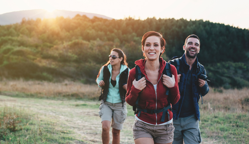 Trio of people out for a hike at sunrise