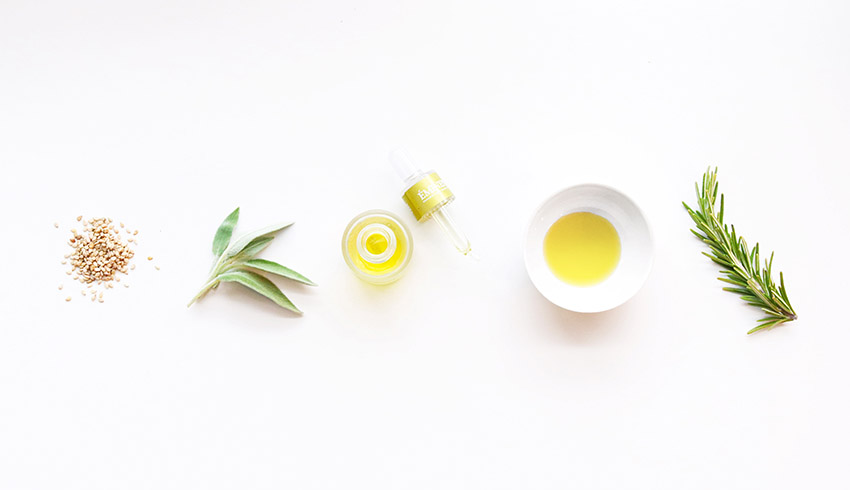 A flatlay featuring Eminence Organics Facial Recovery Oil and herbs