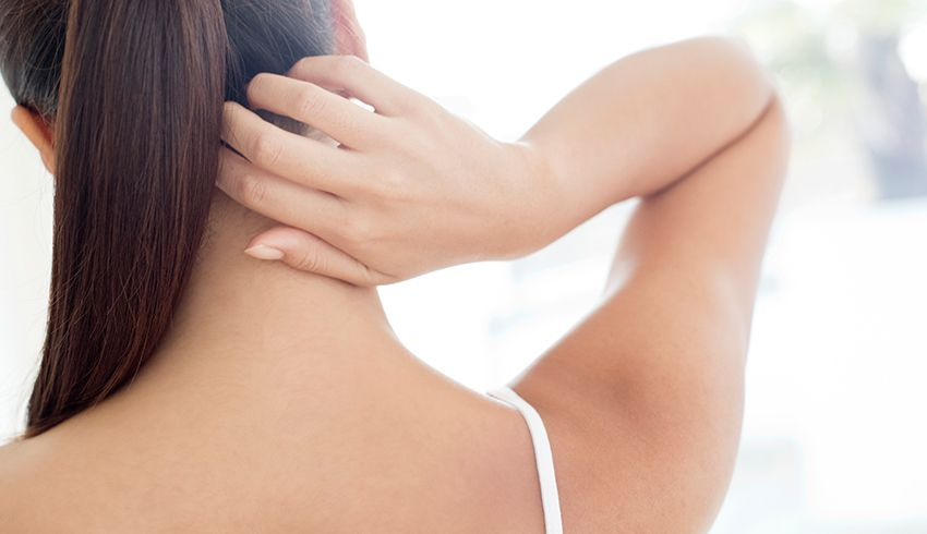 woman with bare back touching neck