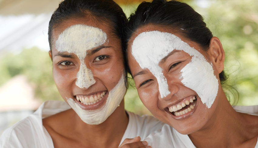 smiling women with clay face masks