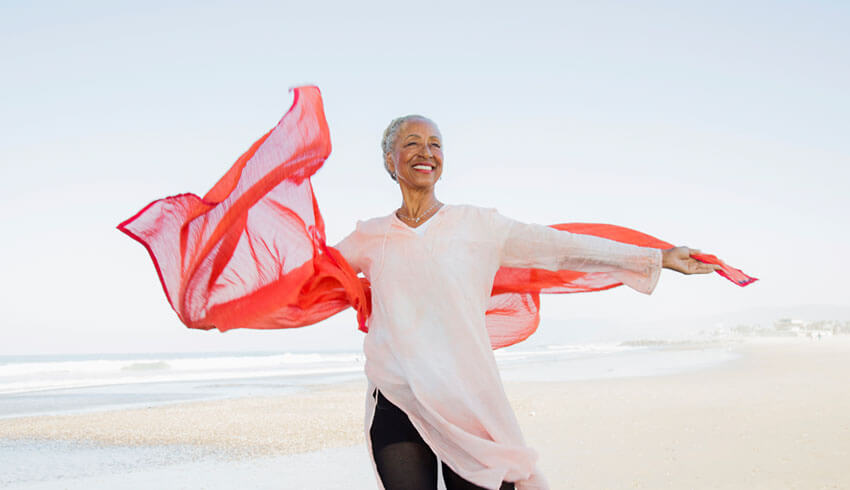 Mature woman with red scarf at the beach