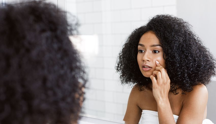 Woman touches her face while looking in the mirror at her reflection