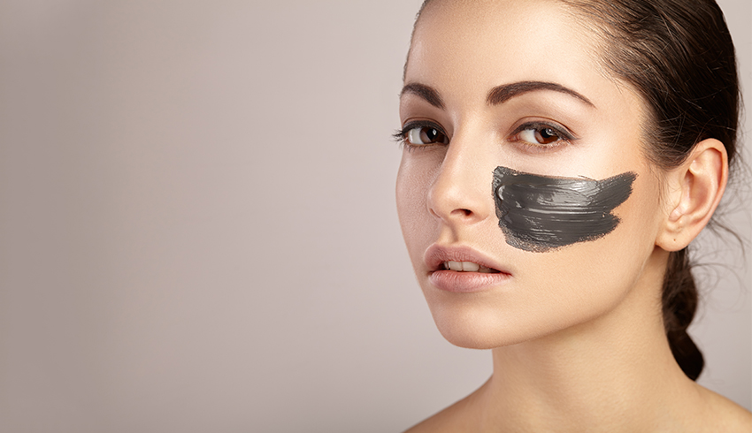 Woman with charcoal face mask on her left cheek