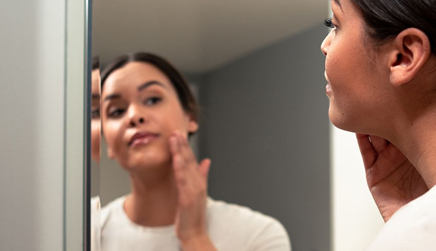 woman applying skin care in mirror