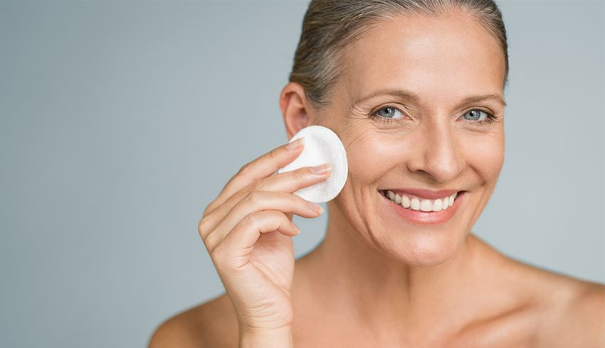 Mature woman pressing cotton round to her right cheek