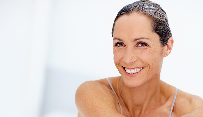 Middle aged woman smiling confidently with eye wrinkles and crow's feet