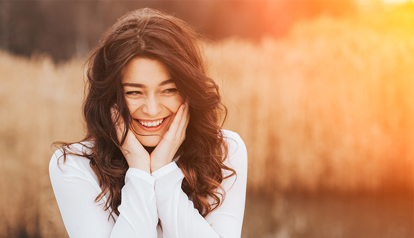 Woman laughing and holding sides of face outside