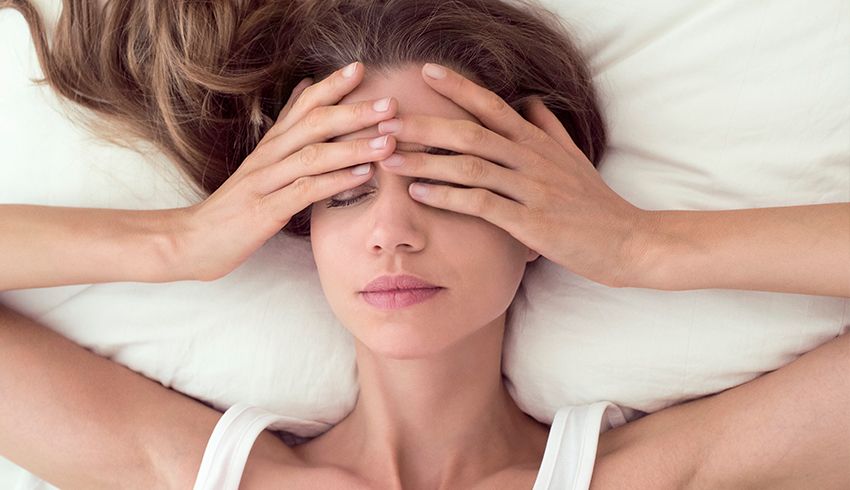 woman lying in bed covering eyes