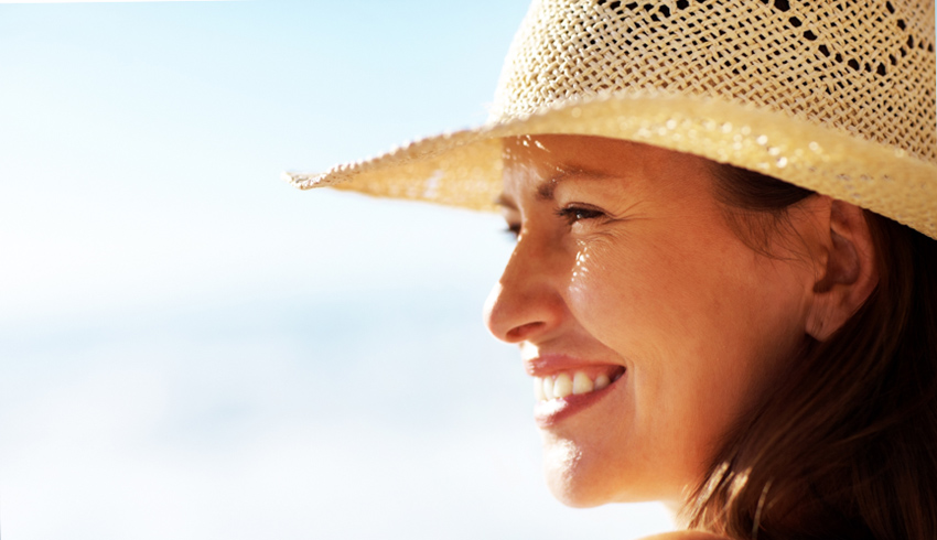 Woman with hat preventing dark spots on face