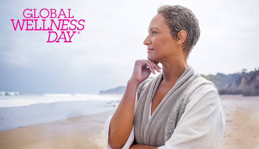 Eminence Organics woman on beach staring at ocean with Gobal Wellness Day logo in top left corner