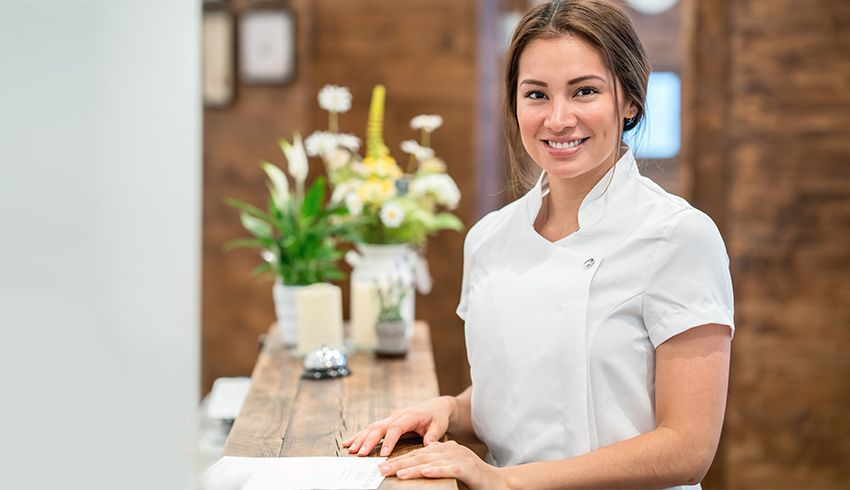 Female esthetician smiles behind front desk
