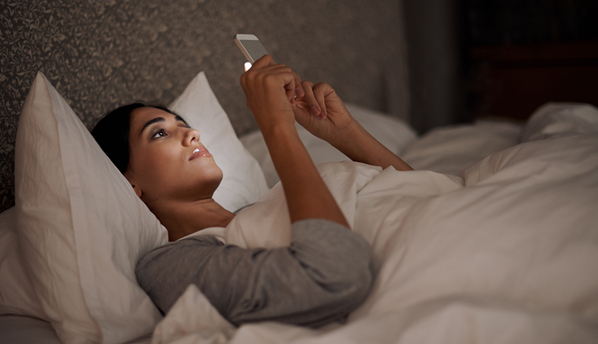 Woman looking at cell phone in bed