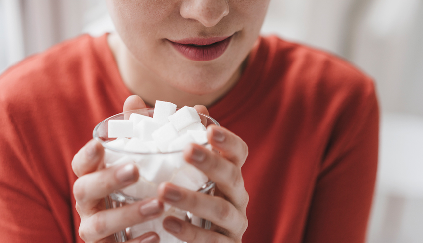 woman holding a cup of sugar cubes