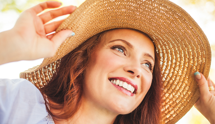 Smiling woman in summer hat protecting her face from the sun