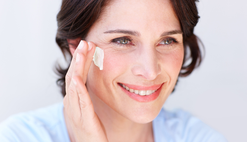 Woman applying Eminence Organics Bright Skin Overnight Correcting Cream