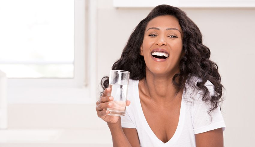 Happy woman drinks water in her bright kitchen