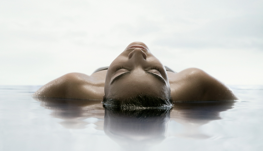 Woman floating in water at the spa