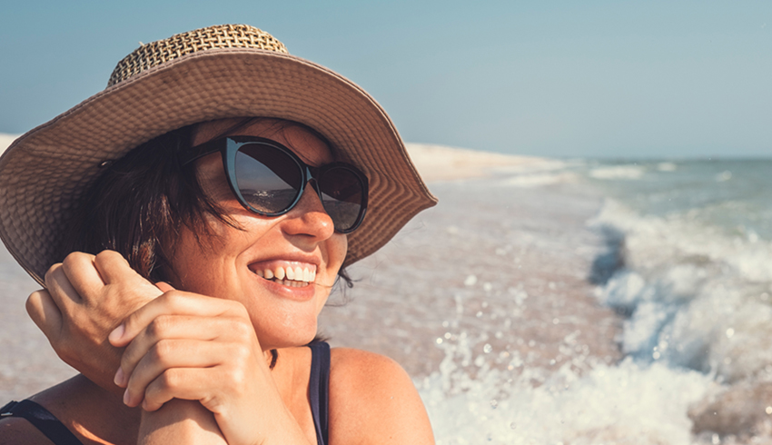 woman in the sun smiling with had and sunglasses on