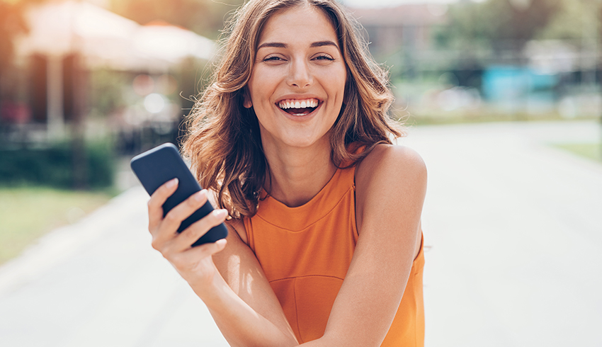 Woman smiling with phone after leaving a review for Eminence Organics