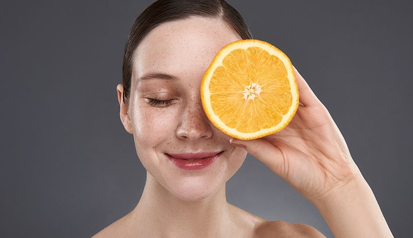 Woman holding orange up to eye