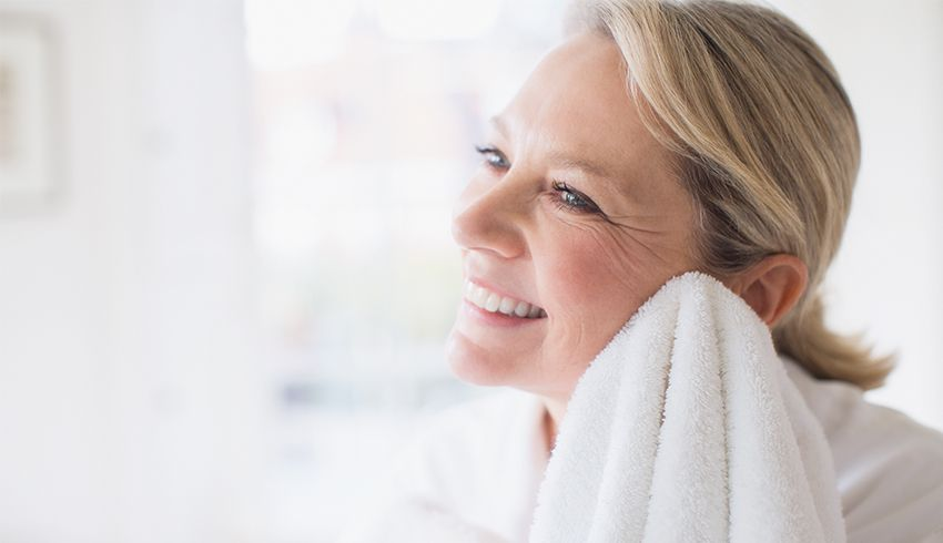 Mature woman drying face with towel and smiling