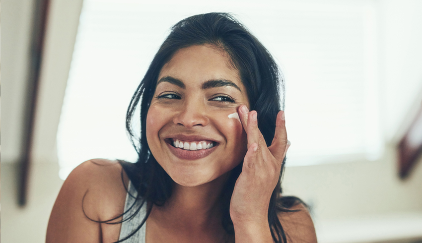 middle eastern woman applies skin care cream