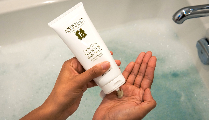 woman squeezing Stone Crop Revitalizing Body Scrub into hand