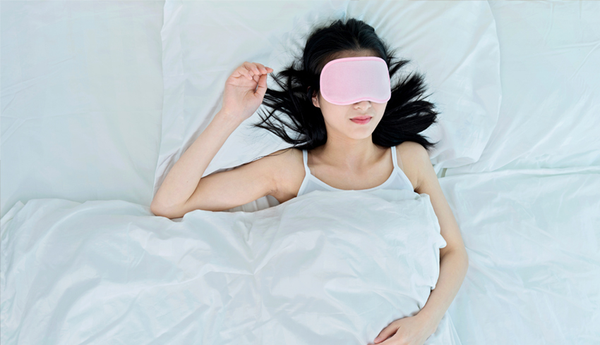 Woman laying in bed wearing a pink eye mask