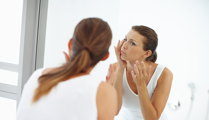 Woman looking in the mirror at the dark circles under her eyes