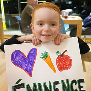 Eminence Kids Foundation child holding up sign