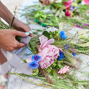 Woman wraps stems of wildflower bouquet