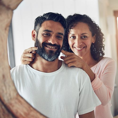 Man with beard looking in mirror with playful woman