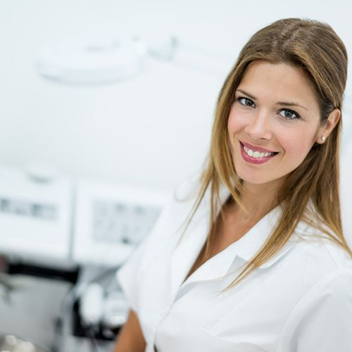 Female esthetician standing beside various treatment machines.
