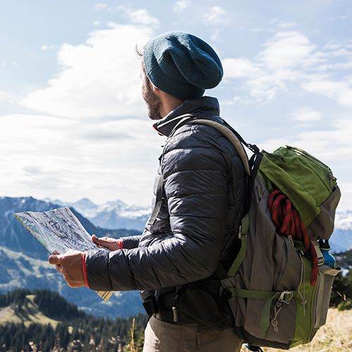 Man with hat outdoors holding map and looking at mountains