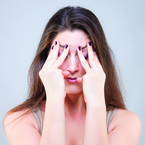 Woman massaging eye brows with both hands