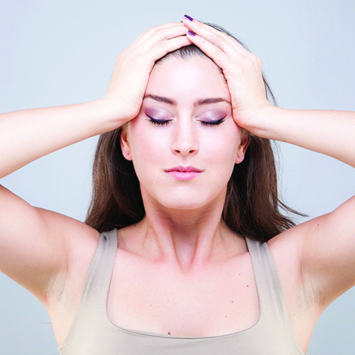 Woman massaging forehead using palms to press into sides of face