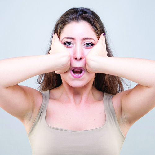 Woman using palms to massage center of face above the mouth