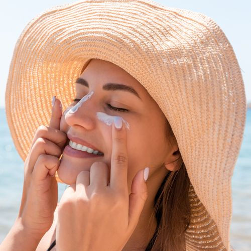 woman in hat putting on sunscreen