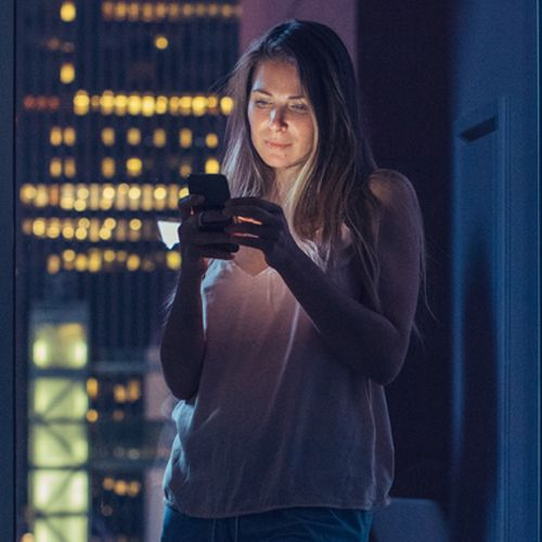 Woman at night looking at phone with blue light