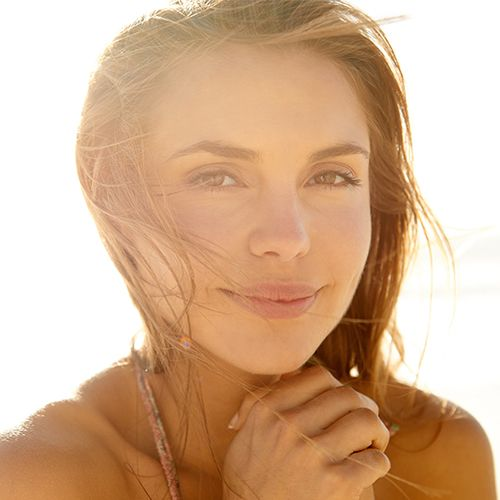Closeup of face of woman on the beach in the sun