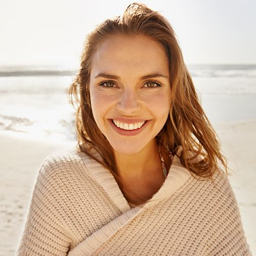 Smiling woman wrapped in beige sweater at the beach.