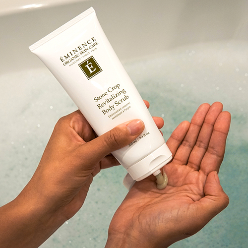 squeezing Stone Crop Revitalizing Body Scrub into hand