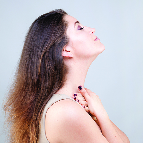 Woman stretching neck and using fingertips to massage the base of neck