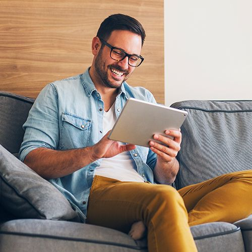 Man with glasses on couch using tablet and smiling