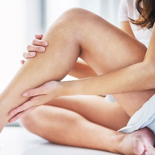 woman applying oil to leg