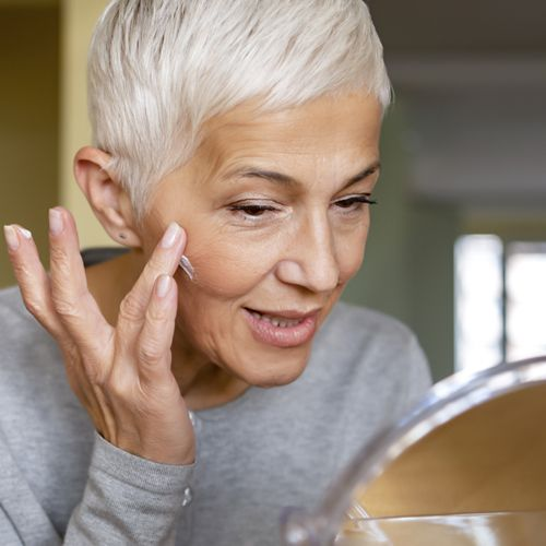 mature woman applying skin care product to treat acne