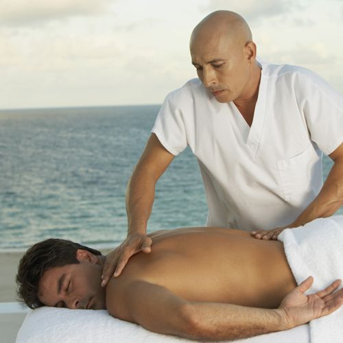 Man getting a back massage next to the water