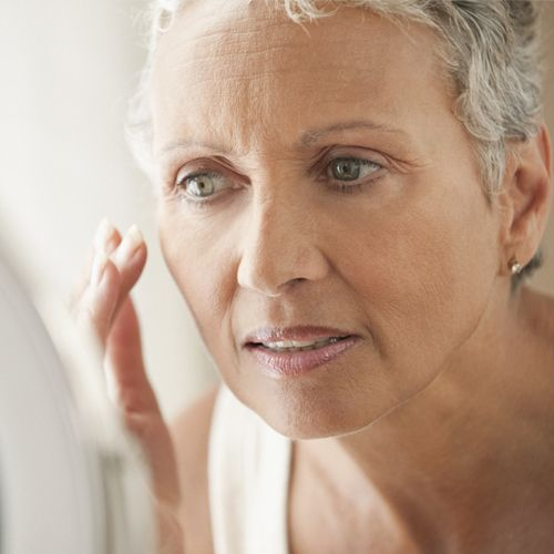 Mature woman demonstrating skin care routine
