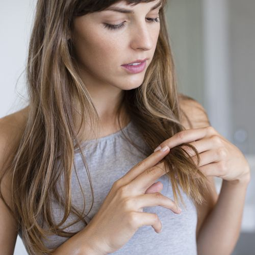 woman looking at dry hair ends